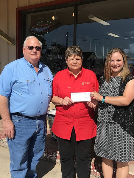 Cuero-Yoakum Propane Gas Co. and The Cooking Depot owners Erwin and Annette Rath (left and center) receive $10,000 check from CDC's Samantha Bayfus (right)