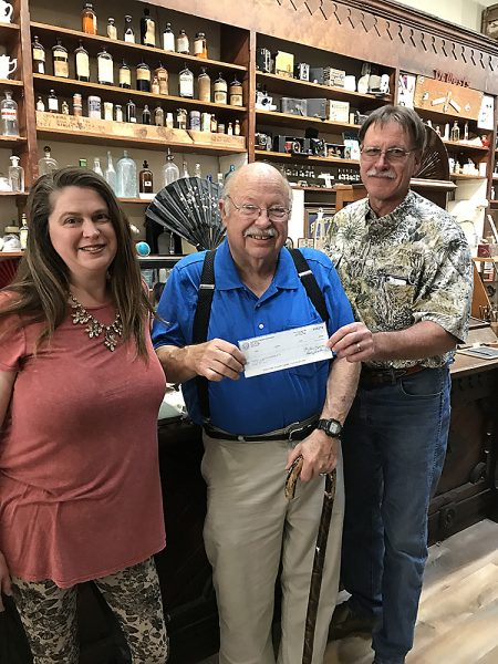 The Pharmacy and Medical Museum of Texas's Amber Fitts (left) and Wayne Adickes (center) receive $2,361 check from the CDC's Dennis Jemelka (right)