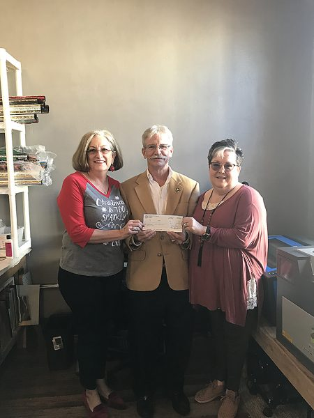A Special Stitch, Inc. owners Sara Gossett (left) and Suzy Adams (right) receive $8,799.15 check from CDC's from Patrick J. Kennedy (center)