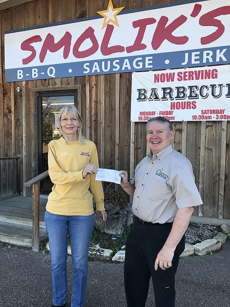 Smolik's Quality Meats & BBQ owner Camille Smolik (left) receives $7,696.86 check from CDC's Randy Jochim (right)