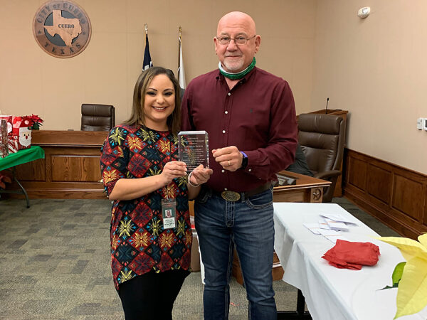 Samantha Bayfus (right) is presented with a plaque by Cuero City Manager Raymie Zella in recognition of her receipt of the City of Cuero 2020 Newton Rath Employee of the Year Award