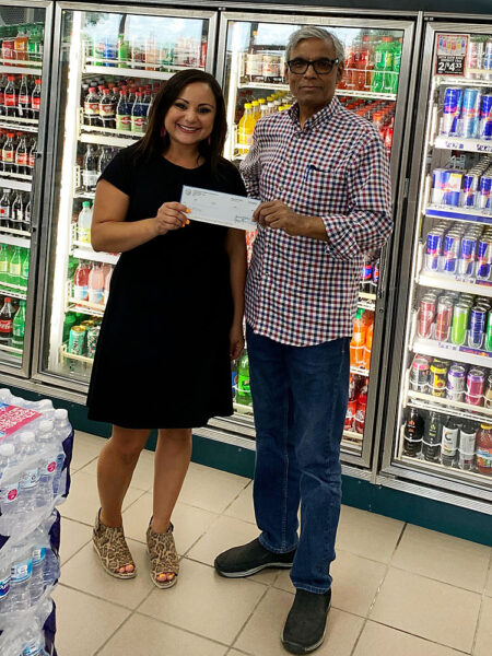 Express Mart owner Nadir Ali (right) receives $10,000 check from the CDC's Samantha Bayfus